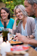 canvas print picture Portrait of a beautiful woman looking at camera, she sits with her friends gathered around a table in the garden one summer evening to share a meal and have fun together.