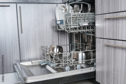 Open dishwasher machine with clean utensils close up