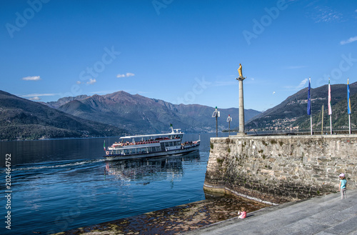 Fotografie, Obraz  a boat sailing in front of the little port of the Madonnina, on Lake Maggiore