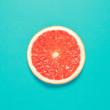 Leinwanddruck Bild - Grapefruit slice on pastel blue background. Minimal summer concept. Flat lay.