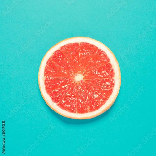 Grapefruit slice on pastel blue background Fototapet