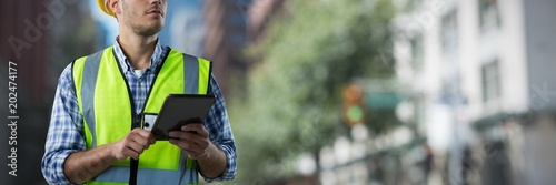 Obraz Composite image of concentrated construction worker with tablet - fototapety do salonu