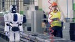 Engineer controls robot working at a conveyor in a factory. 4K.