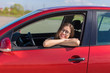 Young woman in car. Girl driving a car. Smiling young woman sitting in red car