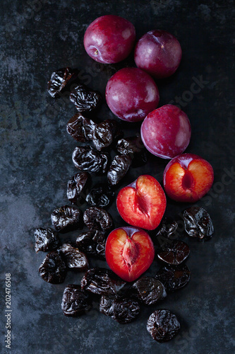 Fresh and dried plums on dark ground