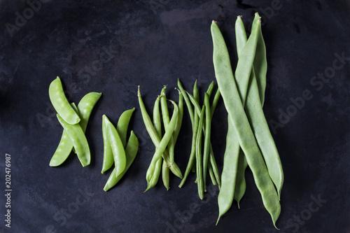 Various sorts of beans and peas on dark metal