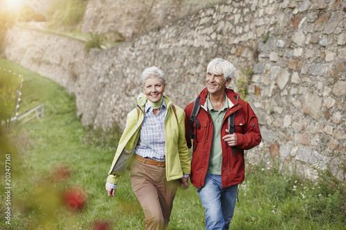 Happy senior couple hiking hand in hand
