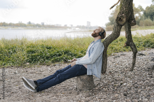 Germany, Duesseldorf, man with smartphone and headphones listening music in nature