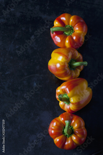 Row of four tiger bell peppers on dark metal