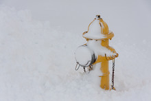 Yellow Fire Hydrant With Snow Piled Up Around It.