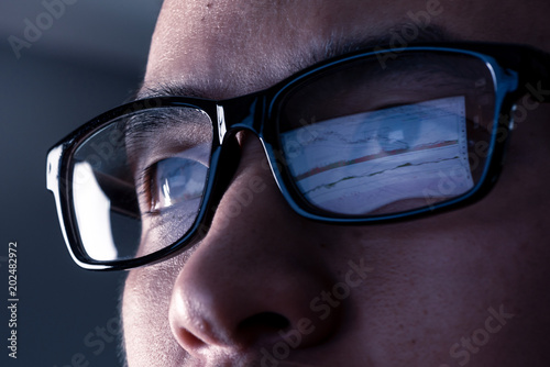 Foto the abstract image of the businessman wear a glasses looking at the stock trading chart on the computer screen