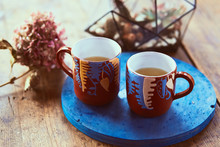 Two Red Cups With Tea Stand On A Blue Plate With Florarium Behind Them
