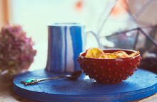 Blue Cup With Tea Stands On A Blue Plate With Florarium And Lemons Behind Them