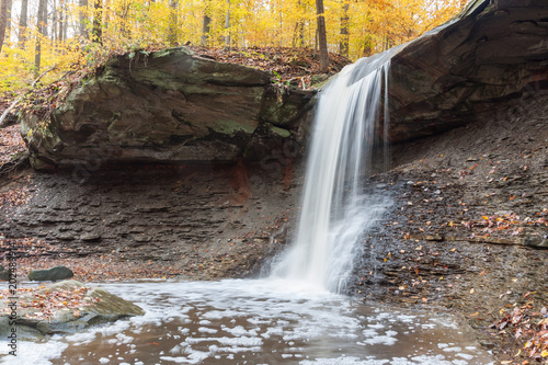 Blue Hen Falls in Cuyahoga Valley National Park. The waterfall is smoothly flowing, with leaves spread on the rocks below. It is autumn, and the trees are yellow.