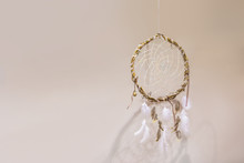 Dream Catcher With White Feathers On A Beige Background In The Interior