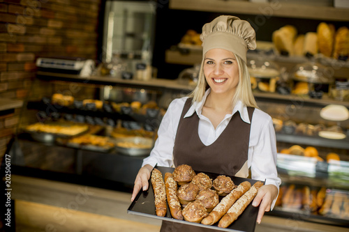 Foto op Plexiglas Bakkerij Female bakery posing with various types of pastries and breads in the bakery