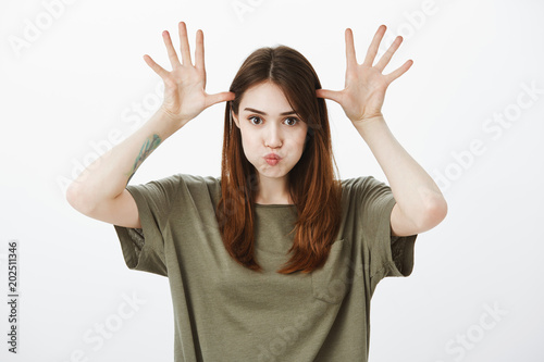 Playful childish adult girl fooling around like child. Carefree positive brunette, sulking, holding palms on head like moose horns, being playful and uplifted, playing with sister over gray wall
