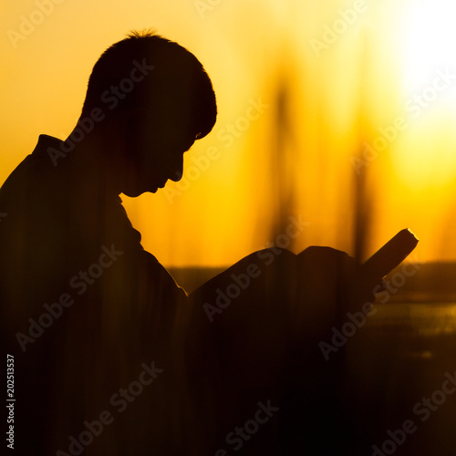 silhouette of a young man with a Bible, male praying to God in nature, the conce Canvas Print