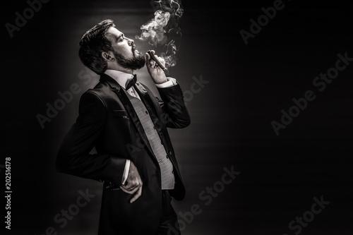 Fotografía portrait of bearded smoking cigar gentleman in a suit