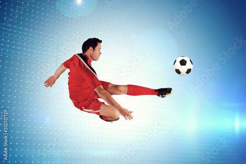 Fotografiet  Football player in red kicking against technical screen with pixels