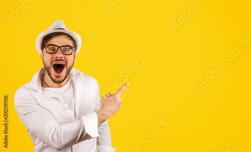 Happy hipster pointing up on yellow