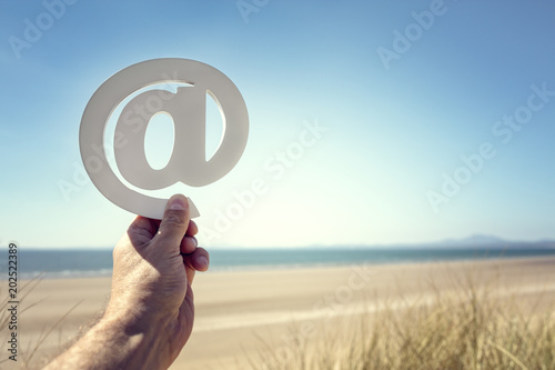 Email at symbol on the beach summer background