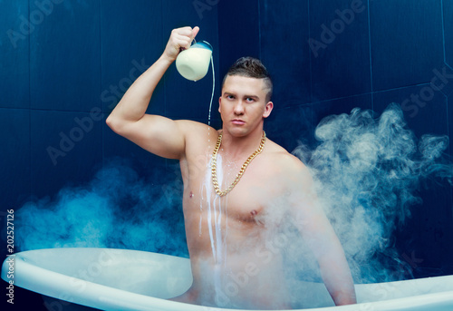 Vászonkép  man taking a bath with milk