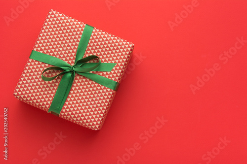 hands holding wrapped gift box with colored ribbon as a present for christmas new year