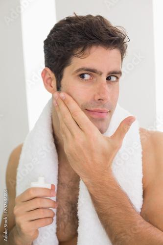 Fotografie, Obraz  Man applying moisturizer on his face
