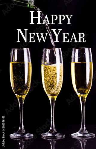 Happy new year against two full glasses of champagne and one being filled
