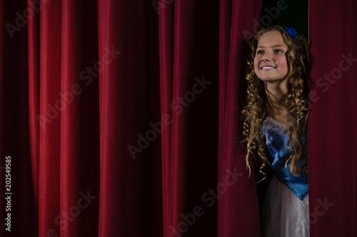Photo  Female artist peeking through the red curtain