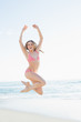 Content young woman jumping on the beach