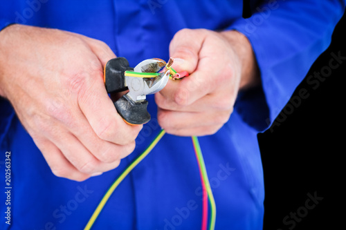 Poster  Electrician cutting wire with pliers against black