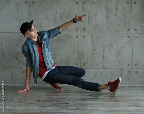 Teenage Boy In Jeans And Red Sweater Denim Jacket And Baseball Cap