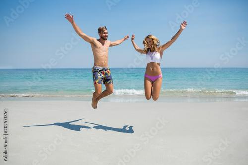Fotografie, Obraz  Playful couple jumping at beach