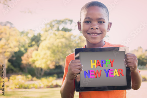 Valokuva  New year greeting against portrait of boy smiling while holding digital tablet