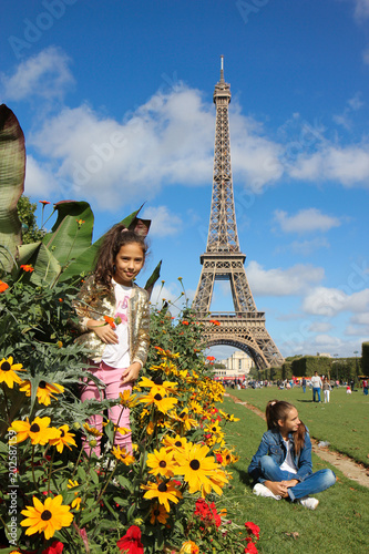 Fotografia  Girls on the field above Eiffel tower