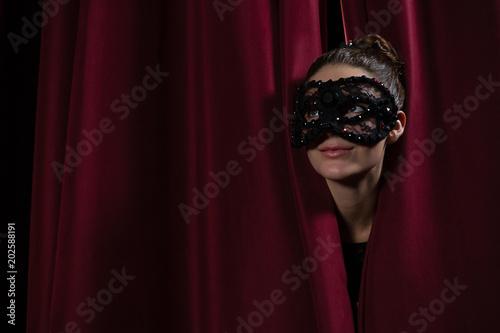 Photo  Female artist in mask peeking through the red curtain