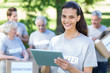 Smiling volunteer brunette using tablet pc