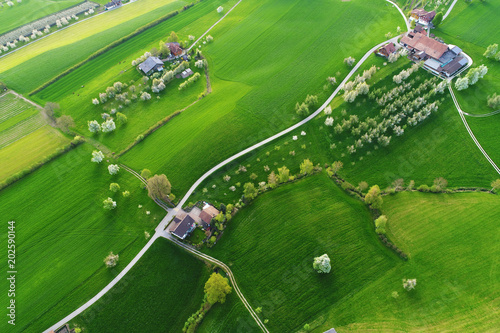 Keuken foto achterwand Olijf Bright green fields with farms from a bird's eye view on a beautiful spring day in central Switzerland