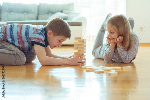 Obraz na plátně Two happy siblings playing a game with wooden blocks at home