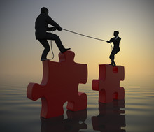 Team Pulling Huge Jigsaw Puzzle Into Position At Sea At Dawn. Two Executives Pull Huge Jigsaw Puzzle Pieces Into Position Demonstrating Teamwork At Sea Since Dawn.