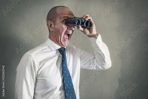 uomo in camicia e cravatta che gurda con il binocolo urlando