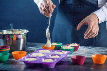 Chef Pastry In A Black Apron Filling The Dough Into A Cupcake Silicone Mold. Concept Of Confectionery Cooking