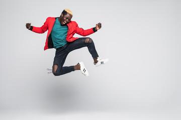 Cijeli portret veselog afroameričkog muškarca koji skače izoliran na bijeloj pozadini