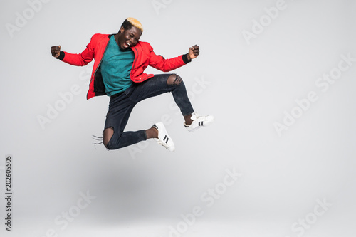 Spoed Foto op Canvas Dance School Full length portrait of a cheerful afro american man jumping isolated on a white background