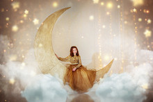 Beautiful Little Girl In Gold Dress, Sits On The Moon In Clouds And Stars