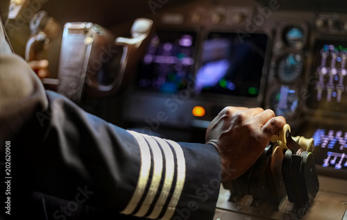 Foto Cropped Hands of African Pilot flying a commercial airplane, cockpit view close