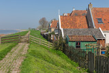 Traditional houses along a dike in Makkum, an old Dutch fishing village in Friesland