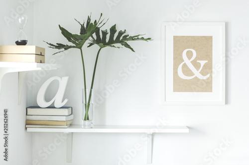 Fotografia Stylish scandi interior with white shelf , mock up frame, books, boxes, hourglass and leafs